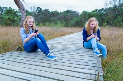 Two girls using social media in nature