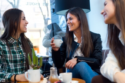 three young women drinking coffee at cafe shop
